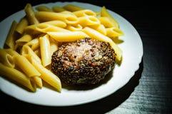 Beefsteack котлет стейка бургера мяса с макаронными изделиями penne на белой плите на темной деревянной предпосылке Стоковое Изображение