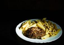 Beefsteack котлет стейка бургера мяса с макаронными изделиями penne на белой плите на темной деревянной предпосылке Стоковое Изображение RF