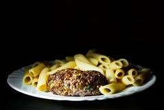Beefsteack котлет стейка бургера мяса с макаронными изделиями penne на белой плите на темной деревянной предпосылке Стоковые Фотографии RF
