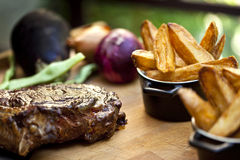 Beefsteak. And french fries on a wooden board stock photo