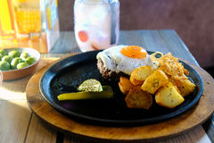 Beefsteak, fried egg, casual meal. High quality photo of delicious homemade style meal: good portion of a beefsteak with fried egg, potatoes and marinated Royalty Free Stock Photo