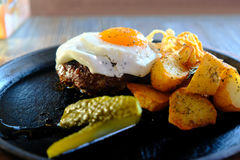 Beefsteak, fried egg, juicy meal. High quality close up photo of delicious `homemade` style meal: good portion of a beefsteak medium rare beef cutlet, a little Stock Photos