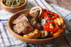 Beefsteak and grilled vegetables with pesto close up on a plate. Stock Photos