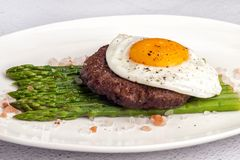 Beefsteak from minced beef with fried eggs and fresh green asparagus stock photography
