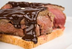 Beefsteak over toast poured chocolate Stock Photos