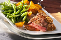 Beefsteak, potato wedges and green beans. Steakhouse meal with rare beefsteak, potato wedges and green beans stock image
