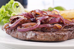 Beefsteak with roasted Onion Rings Royalty Free Stock Photos