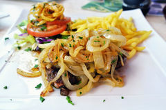 Beefsteak. Served on white plate with caramelized onions, tomatoes, fried potatoes stock photo