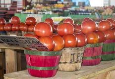 Beefsteak tomatoes in basket. Beefsteak tomatoes displayed in a farmers market, in wooden baskets stock photo