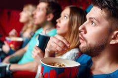 Beeindruckte Kinozuschauer mit Popcorn Lizenzfreie Stockfotos