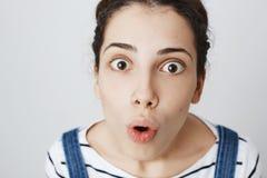 Beeindruckte und überraschte Frau mit der durchbohrten Nase, oben betrachtend Kamera mit verbreiterten Augen und geöffnetem Mund  lizenzfreie stockfotografie