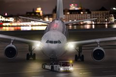 Beeing dell'aeroplano rimorchiato ad un aeroporto a comporre di notte immagine stock