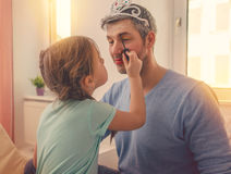 Beeing a little make-up artist. Dad with cute daughter beeing treated with lipstick for carnival royalty free stock image