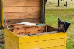 Beekeeper's-Werkzeug, das Rauch auf dem geöffneten gelben Bienenstock macht Stockfoto