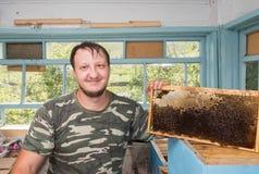 Beekeeper держа в сотах пчелы рук воска в деревянной рамке Стоковая Фотография RF