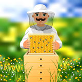 Beekeeper on apiary. A man in a white beekeeper suit works near a beehive. Sunny summer day on a flowering meadow. Stock Photo