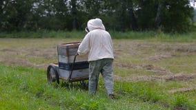 Beekeeper carries a frame of honey on a metal cart