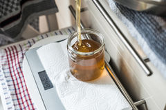 Beekeeper filling up the fresh golden new honey into glass jars on a scale scales. Beekeeper filling up the fresh new honey into glass jars on a scale scales Stock Images