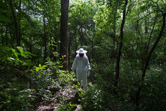 Beekeeper in the forest. Horizontal front view of beekeeper in white protection suit standing in a green forest Royalty Free Stock Photography