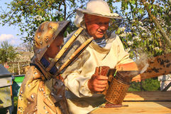 Beekeeper grandfather and grandson examine a hive of bees Stock Photos