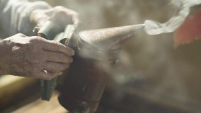 Beekeeper holding bee smoker. Beekeeper holding steaming bee smoker. Instrument to fumigate beehives and bees stock footage