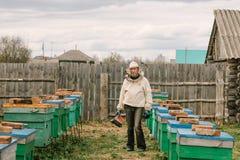 Beekeeper i en skyddande dräkt bland bikuporna royaltyfri foto