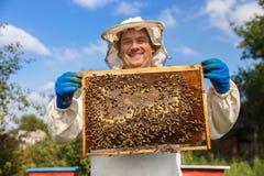 Beekeeper med honungskakan Royaltyfria Bilder