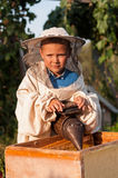 Beekeeper portrait of a young boy who works in the apiary at hive with smoker for bees in hand Royalty Free Stock Photo