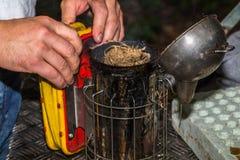 The beekeeper prepares a smoker Stock Photos