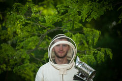 Beekeeper with smoke tool. Beekeeper in a protective suit with smoke tool Royalty Free Stock Photos
