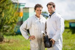 Beekeepers With Smoker Standing At Apiary. Portrait of happy male and female beekeepers with smoker standing at apiary Stock Photos