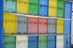 Beekeeping - Beehives. Beekeeping: A long line of coloured beehives in the middle of a meadow royalty free stock photo