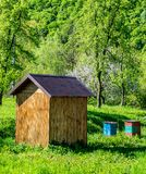 Beekeeping in the garden. Beekeeping in garden. Few multicolored beehives and wooden shed on a green grass royalty free stock photos