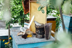 Beekeeping.Pasika honey honeycomb. Metal bee smoker smokes on an apiary with smoke stream.Honeycombs.Honey cutting knife royalty free stock images