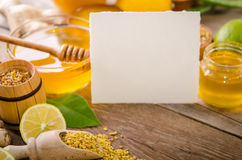 Beekeeping products with lemons on a wooden table. With empty card for you text . side view royalty free stock image