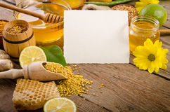 Beekeeping products with lemons on a wooden table. Beekeeping products on a wooden table with empty card for you text . side view royalty free stock images