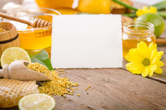 Beekeeping products with lemons on a wooden table. With empty card for you text . side view royalty free stock images