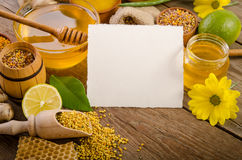 Beekeeping products with lemons on a wooden table. With empty card for you text . side view stock image