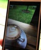Beeld die in de telefoon van hete cappuccinokoffie schieten in witte kop en schotel zachte nadruk op houten lijstachtergrond royalty-vrije stock afbeeldingen
