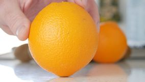 Beeld die met Mensenhand op Keuken een Mooi Oranje Fruit voorstellen stock afbeelding
