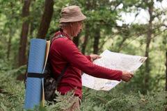 Beeld die van de oude mens, hebbend actieve rust, bestedend zijn roeping backpacking het reizen, die zich met kaart bevinden, pro stock fotografie