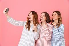 Beeld die van drie leuke vrouwenjaren '20 kleurrijke gestreepte pyjama dragen Royalty-vrije Stock Afbeelding