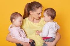 Beeld die van moeder met haar zoete kinderen, in studio stellen Brij en meisjes terloops de geklede tweelingen, mamma vertelt ong royalty-vrije stock foto's