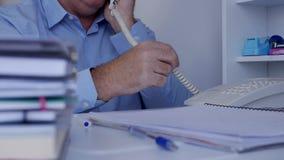 Beeld met een Businessperson in Archief die een Telefoongesprek maken die Bureaulandline gebruiken stock videobeelden