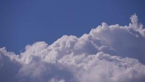 Beeld in real time met witte cumulonimbus pluizige wolken die zich op blauwe hemel bewegen stock video