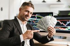 Beeld van aantrekkelijke het geldventilator van de zakenmanholding terwijl het werken in bureau met grafiek en grafieken aan comp royalty-vrije stock afbeelding