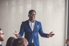 Beeld van Afrikaans-Amerikaanse bedrijfsleider die camera in werkomgeving bekijken Stock Foto's