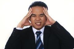 Beeld van beklemtoonde jonge Aziatische zakenman die problemen en hoofdpijn hebben Royalty-vrije Stock Foto