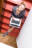 Beeld van blonde jonge mooie zaken of vrouwelijke student die pret het werk het typen op laptop computer ontspannende zitting heb Stock Afbeeldingen