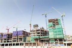Beeld van bouwwerf tegen blauwe hemel met veelvoudige torenkranen Royalty-vrije Stock Foto's